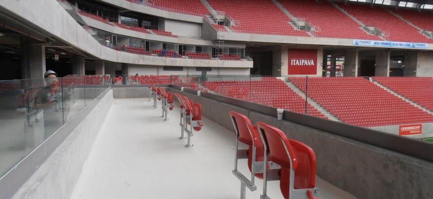 Foto da área para pessoa em cadeira de rodas. Vemos alguns assentos vermelhos para acompanhantes e espaços livres que serão ocupados por cadeirantes.